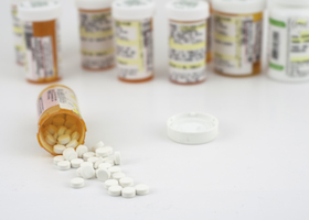 Photograph of a spilled pill bottle with additional medications in the background.